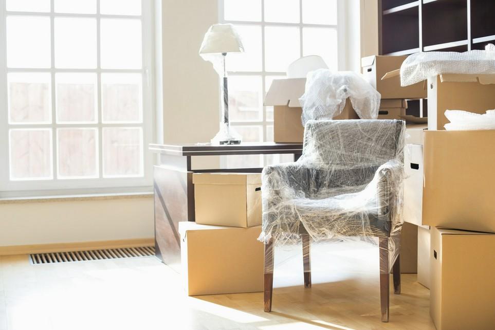 Das Bild zeigt Umzugskartons und verpackte Möbel in einer neuen Wohnung.