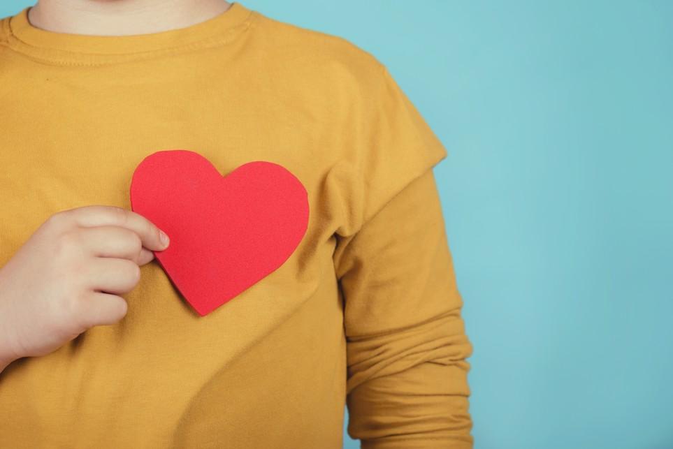 Ein Kind hält sich ein rotes Herz aus Papier an die Brust.