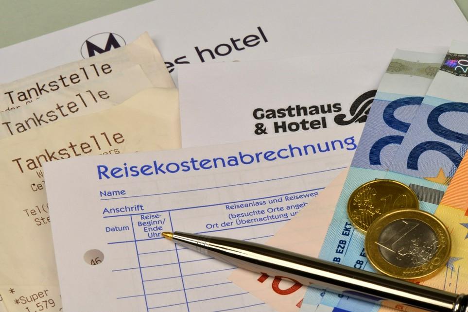 Belege für Hotelübernachtungen und Quittungen von Tankstellen liegen vorbereitet sortiert unter einer Reisekostenabrechnung, Kugelschreiber, Geldscheinen und Münzen als Vorbereitung für die Steuererklärung.